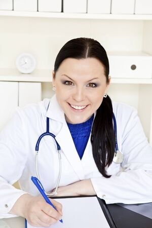 doctor woman making notes in surgery office photo
