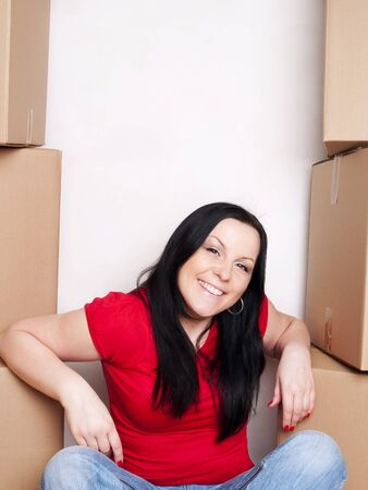 smiling woman sitting with cartons and moving in Stock Photo - 6998364