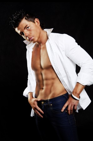 muscle shirt: hombre apuesto joven en camisa blanca posando sobre fondo oscuro