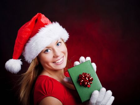young christmas woman holding present over dark background photo