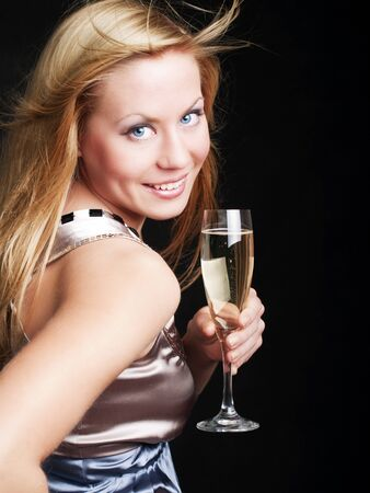 smiling young woman with sylvester champagne over dark background photo