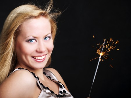 smiling young woman holding new year's sparkler over dark background Stock Photo - 7957164