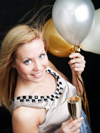 smiling woman holding new year's champagne and balloons over dark background Stock Photo - 7957162