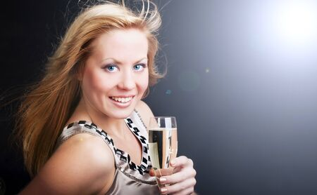 sylvester: smiling young woman with sylvester champagne over dark background Stock Photo
