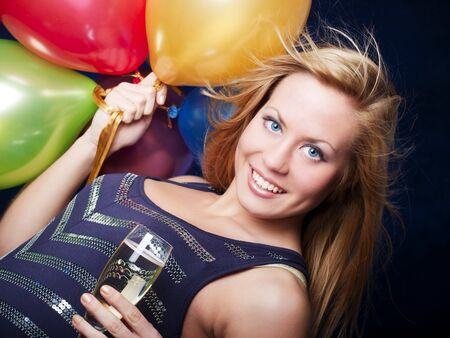 smiling woman holding new years champagne and balloons over dark background photo