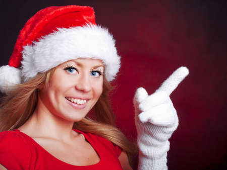 young christmas woman pointing space over dark background photo