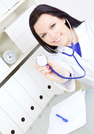 smiling doctor woman holding stethoscope in office photo