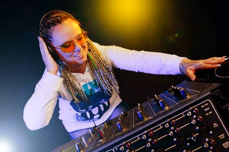 crossfader: smiling dj woman playing music by mikser Stock Photo