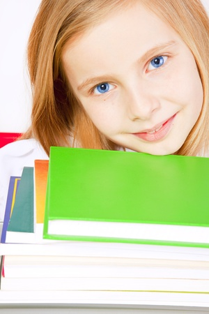 closeup of smiling small girl with books on table