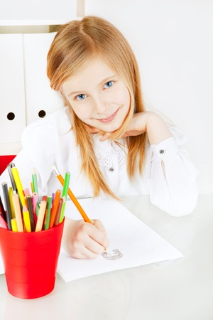 small smiling girl painting picture on table photo
