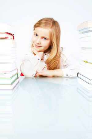 small smiling girl with books in library photo