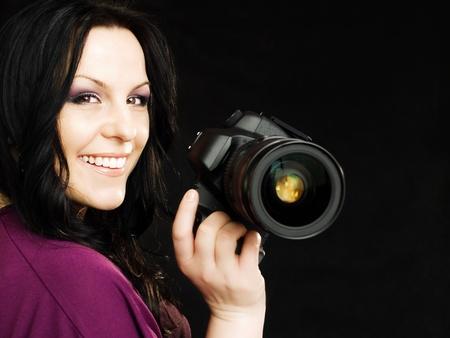 brunette fotograaf vrouw bedrijf camera glimlachen op donkere achtergrond