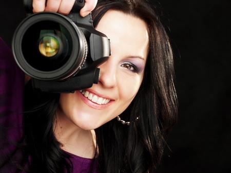 暗い背景上のブルネット カメラマン女性保持しているカメラの笑顔