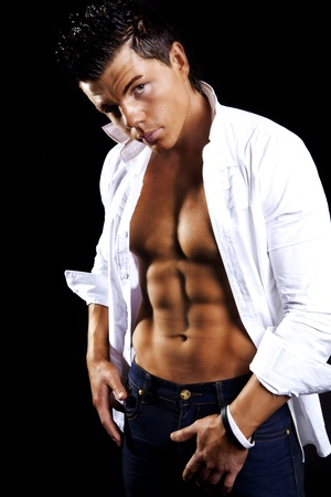 young handsome man in white shirt posing over dark background photo