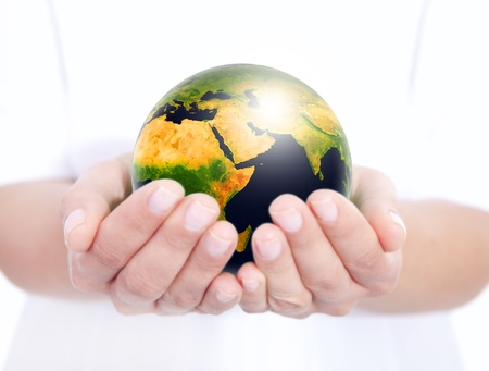 closeup of shining globe holded in human hands. focus on globe photo