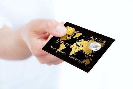 白い背景の上の手によって折り畳みゴールドのクレジット カード