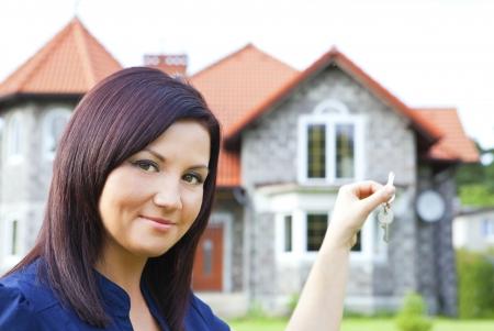 バック グラウンドで家を持つ女性保持キーの笑みを浮かべてください。
