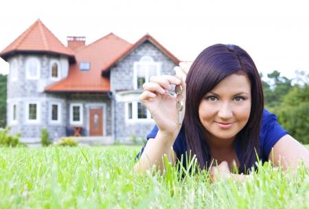 lachende vrouw met sleutels met huis in achtergrond
