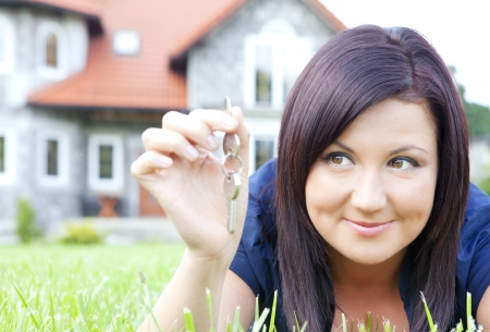 smiling woman holding keys with house background photo