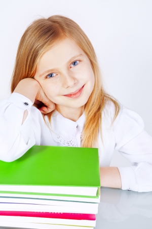 small smiling girl with books in school photo