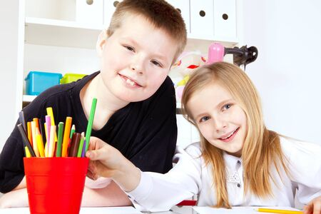 two small children in school painting drawings photo