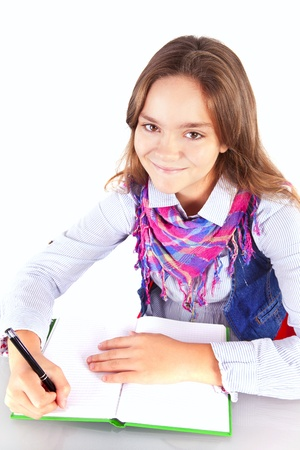 smiling girl doing homework isolated over white backgorund photo