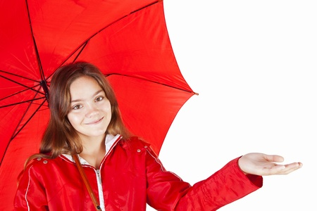 smiling girl dressed in raincoat holding umbrella over white background Фото со стока