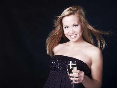 brindisi spumante: bella donna bionda celebrare nuovo anno vigilia champagne su sfondo scuro Archivio Fotografico