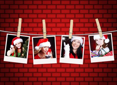 photos of christmas girls hanging on clothesline with brick wall background photo