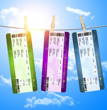 boarding pass tickets hanging on clothesline isolated over blue sky photo