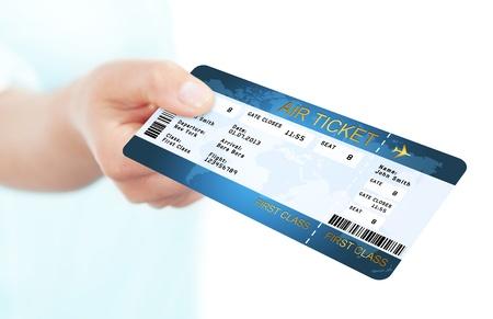 白い背景の上の手で折り畳みの青いフライ航空券 写真素材