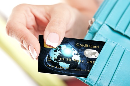 cash card: credit card in womans hand taken out from wallet in the shop