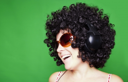 smiling woman with afro hair listen to music with headphones  over green background photo