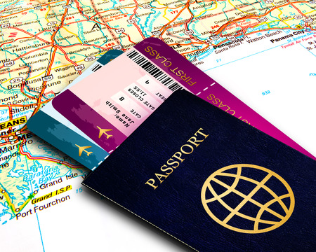 passport and first class fly tickets over map