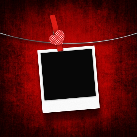 photo hanging on clothesline with heart clothespin over grunge background