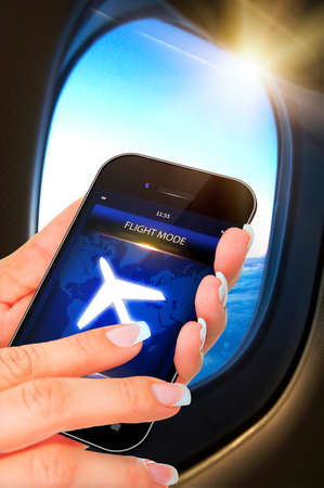 flight mode: closeup of hand holding mobile phone with flight mode in the airplane
