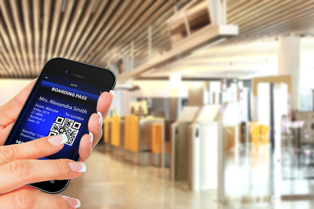 hand holding mobile phone with mobile boarding pass on airport photo