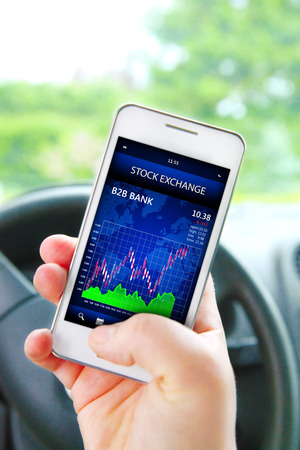 hand holding cellphone with stock exchange screen  focus on screen   photo