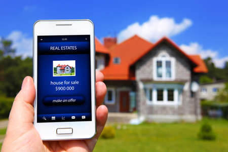 house prices: hand holding mobile phone with house sale offer and house as a background