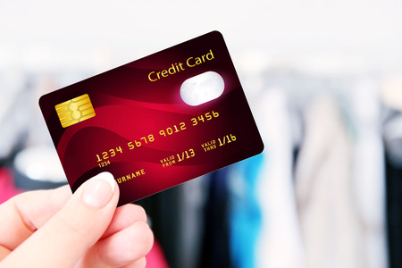 non cash: hand holding credit card in the shop. focus on card
