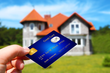 hand holding credit card with house as a background. focus on card. Stock Photo