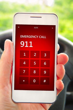 hand holding mobile phone with emergency number 911. focus on screen photo