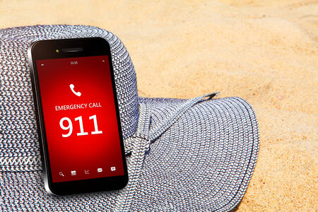 emergency number: mobile phone with emergency number 911 on the beach. focus on screen Stock Photo