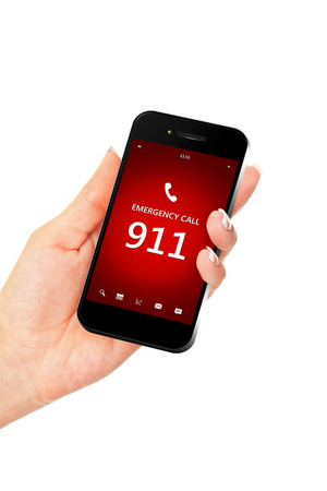 911 の緊急電話番号を持つ携帯電話を持っている手。画面に焦点を当てる