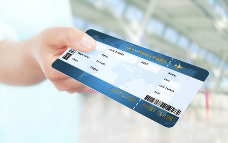 flight ticket: first class flight ticket holded by hand. focus on ticket