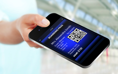 boarding: hand holding mobile phone with mobile boarding pass on airport. focus on mobile phone