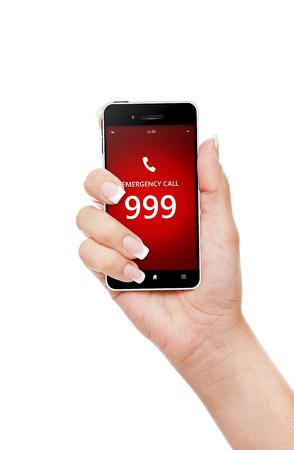 999 の緊急電話番号を持つ携帯電話を持っている手。画面に焦点を当てる