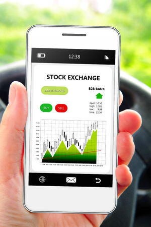 stock car: hand holding cellphone with stock exchange screen. focus on screen. Stock Photo