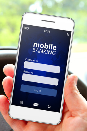 mobile security: hand holding mobile phone with banking log in page in the car Stock Photo