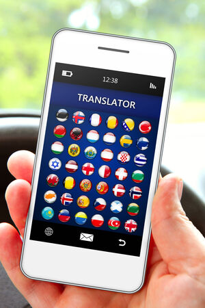 lingua: hand holding mobile phone with language translator application in the car